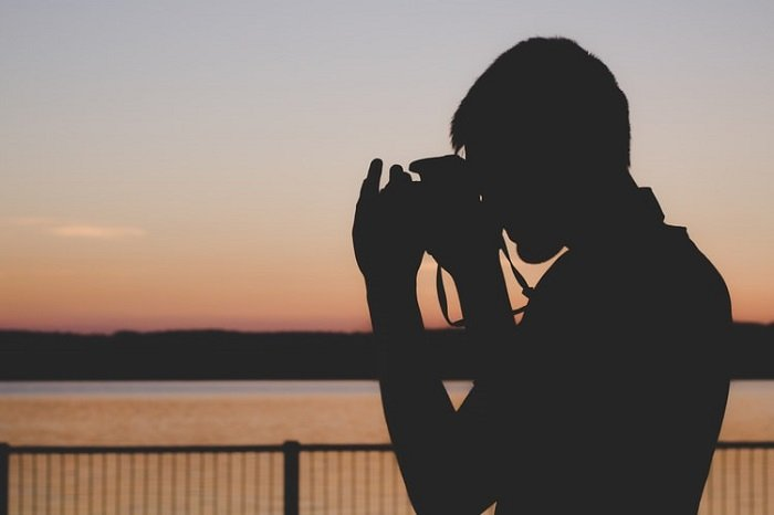 photographer looking out over a body of water at sunset