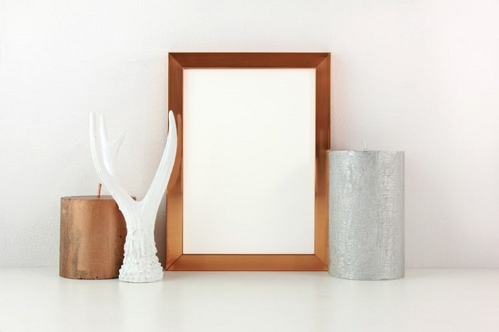 empty photo frame with candle decorations on either side