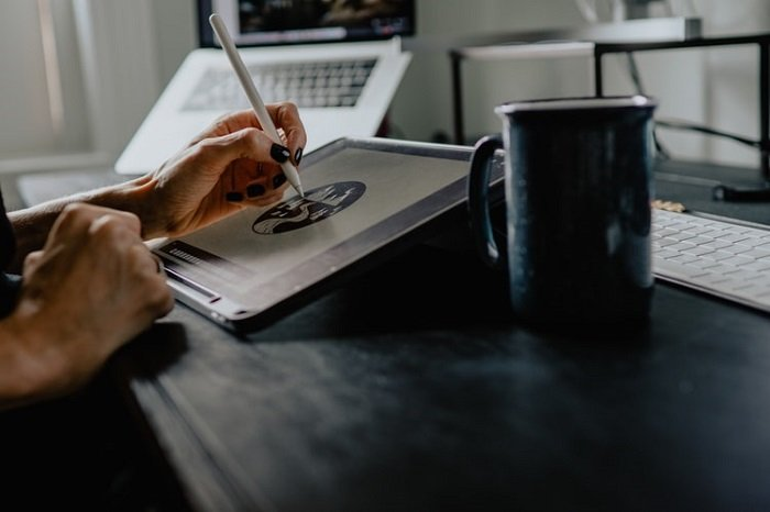 graphic designer working on a tablet with a stylus and a cup of coffee in the foreground