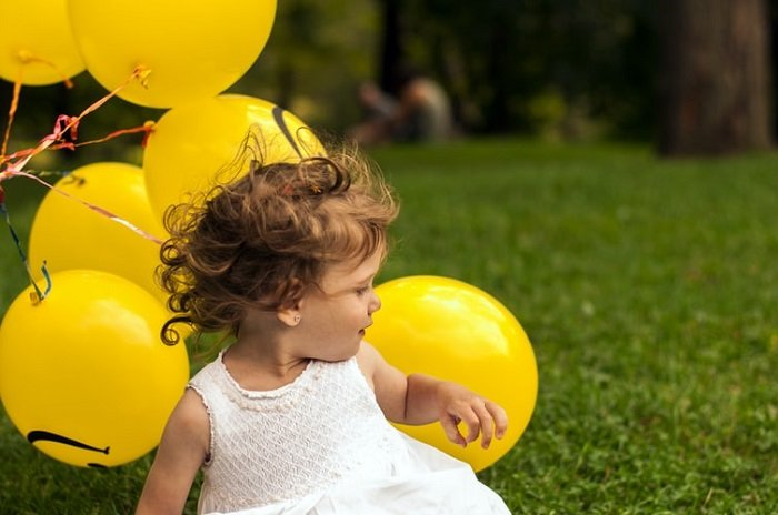 child photography in a candid shot with a green field and yellow balloons