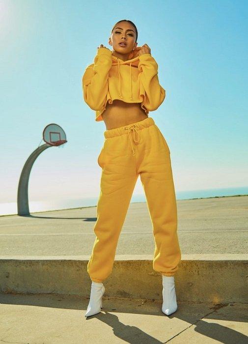 model wearing yellow athleisure fashion next to a basketball court