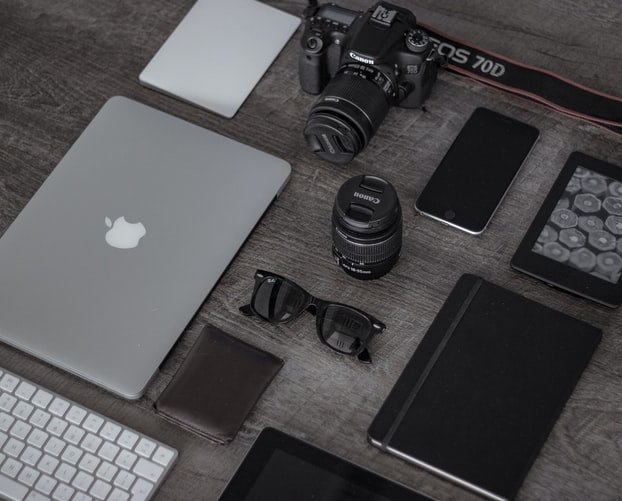 camera and lens surrounded by useful photography tools