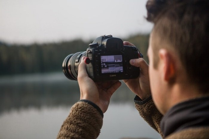 photographer taking a picture with a blurred lake in the background