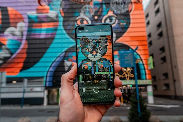taking a photo of colourful street art of a cat using a smartphone