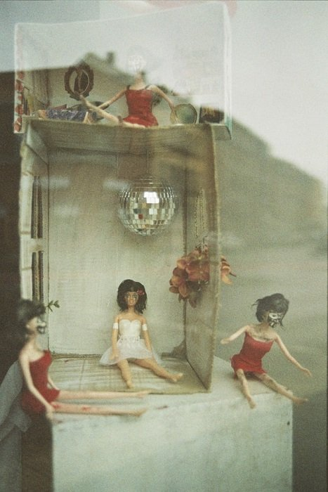photograph of a small dollhouse shot on expired film, with a grey hue and film grain