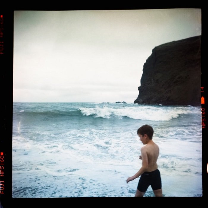 photograph of boy on a beach shot on expired film