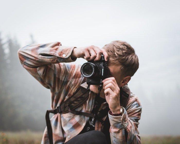一名男子拿着富士相机和镜头在外面照相
