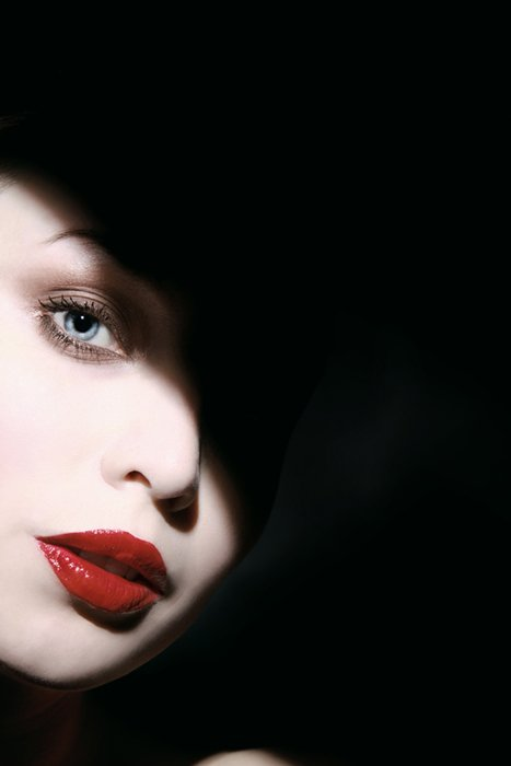 Portrait or a woman with white make-up red lips and a shadow across her face taken with hard light