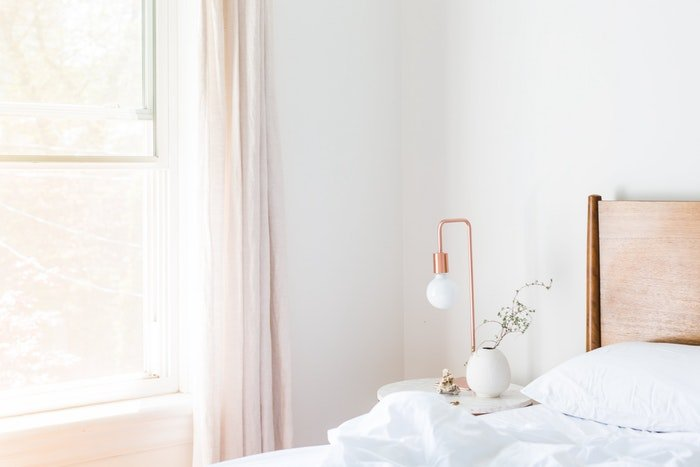 A bright white room with a bed window and night stand shot by a real estate photographer
