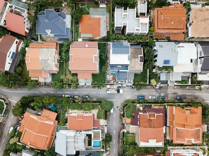 Overhead aerial view showing roofs and yards of houses, and streets in a niegbourhood shot by a real estate photographer