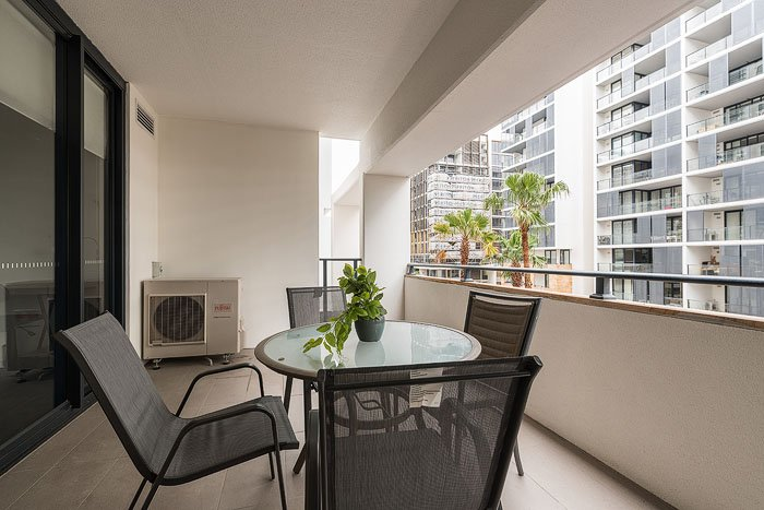 An apartment balcony with chairs, a table, and a view of buildings shot for real estate photography