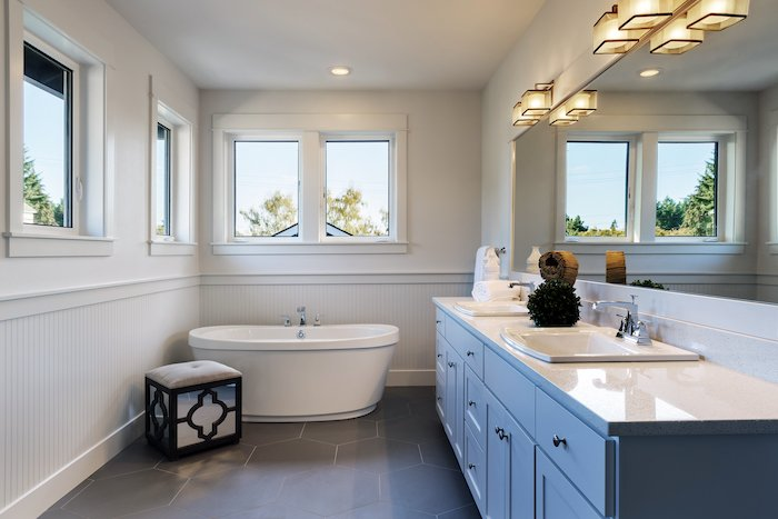 A bathroom with a bathtub and sinks shot for  real estate photography