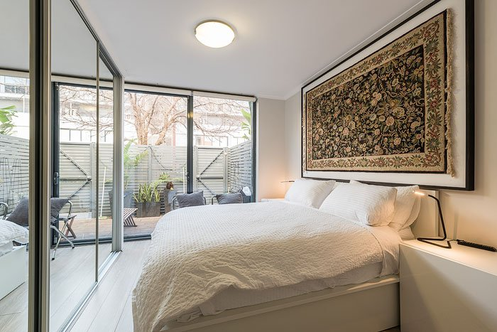 Interior of a bedroom with a closet mirror and large windows shot for how to get into real estate photography