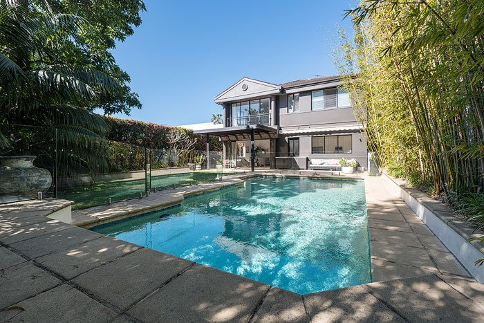 A swimming pool in the foreground of a large house shot by a real estate photographer
