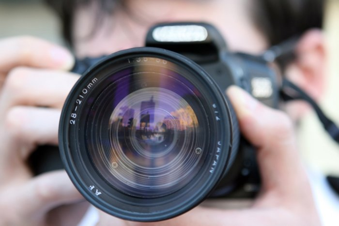 A person looking through a camera lens with lens elements