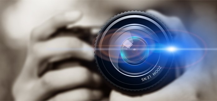 A person looking through a camera lens with selective focus lens flare