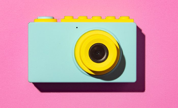 A closeup image of a camera against a pink background