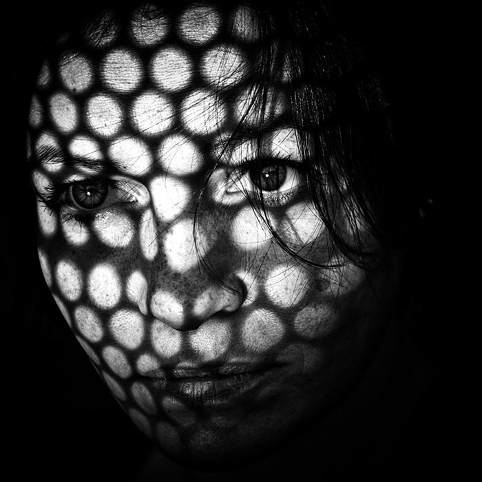A portrait of a woman with a patterned grid of light and shadow illuminating parts other face