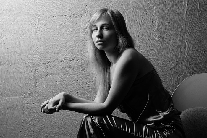 A black and white portrait of a woman sitting with soft light bouncing off the wall behind her
