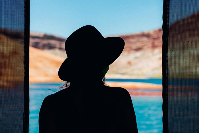 A silhouette of a woman and drapes against a blurred water and landscape