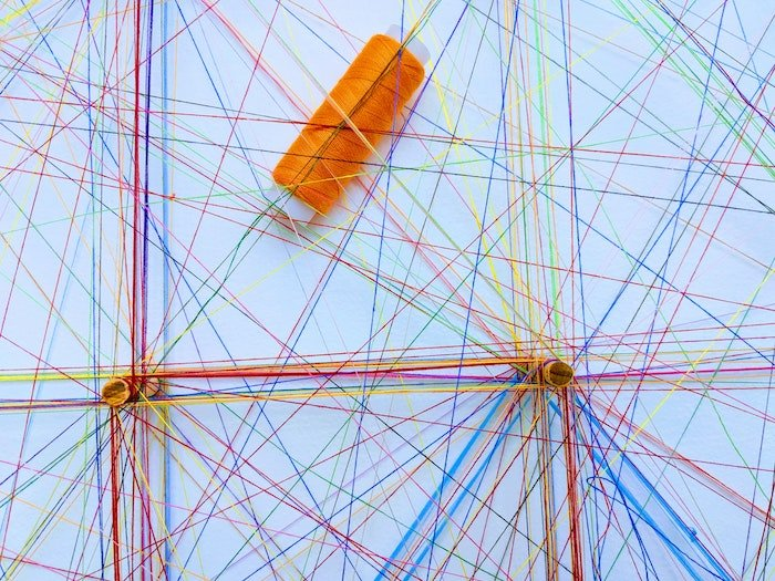 A spool of orange thread on a surface with strings of colored thread intertwined and criss-crossing in different directions