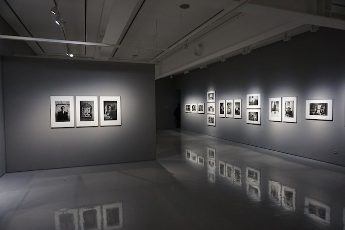An art gallery space with gray walls and white-framed photos on the wall in spotlights