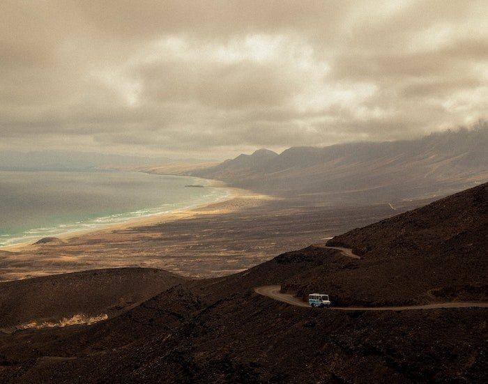 Landscape image of a cloudy coastline with aa beach, ridge lines, and a road with a vehicle on it