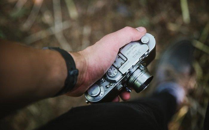 man holding a compact camera