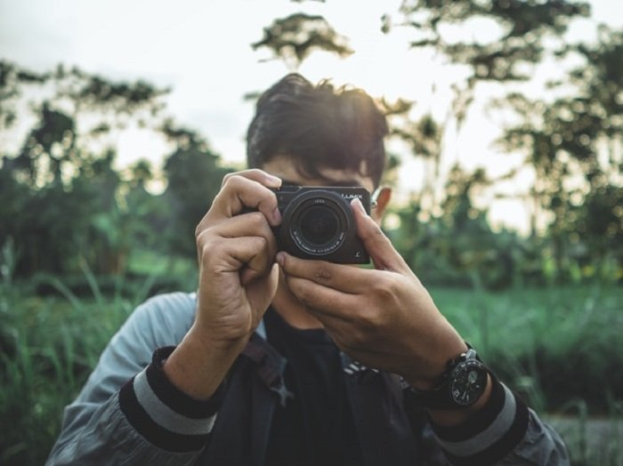 photographer holding a compact camera