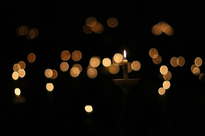 A nighttime image of a lit candle with soft candlelight bokeh in the background