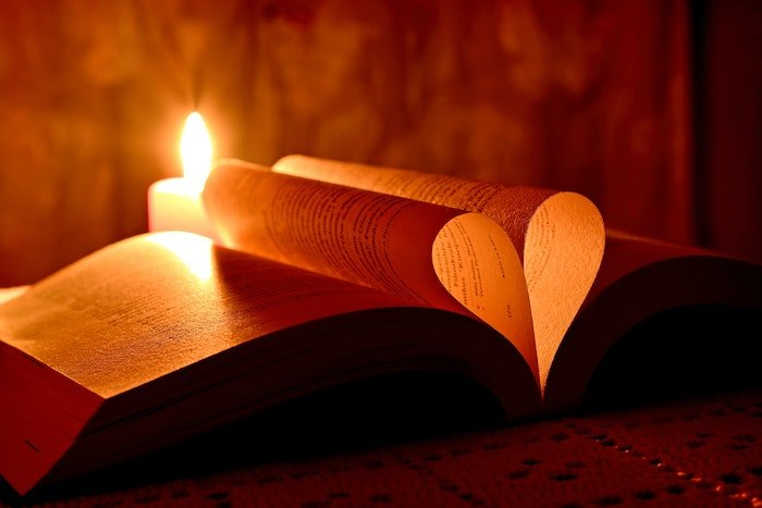 A book with pages folded in the shape of a heart backlit by a lit candle