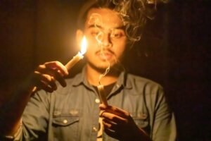 A candlelight photo of a person holding one lit candle and one candle with smoke trailing off the wick