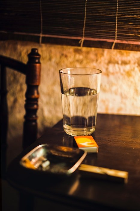 A glass of water on a table shot by candlelight