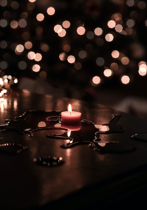 A lit tea light on a table of melted wax with soft bokeh in the background