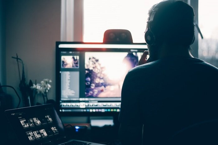 over the shoulder view of man using editing software