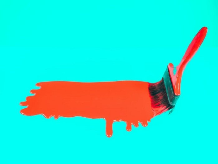 paint brush with red paint on a bright background