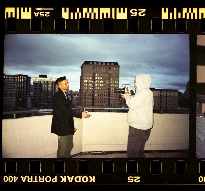 摄影师在城市摩天大楼前拍摄模特的影片