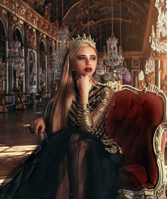 fantasy photograph of a queen posed on a throne in a grand hall