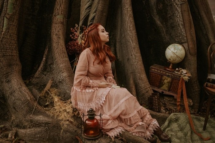 fantasy setting of a woman in a pink dress beside a large tree