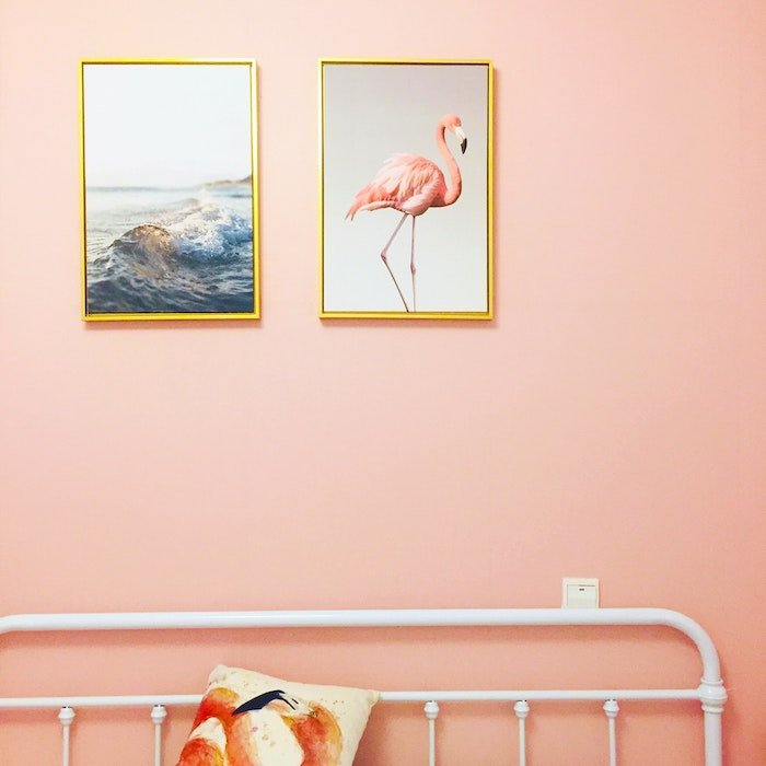 Enlarged printed and framed photos of the ocean and a flamingo hung above a bed frame