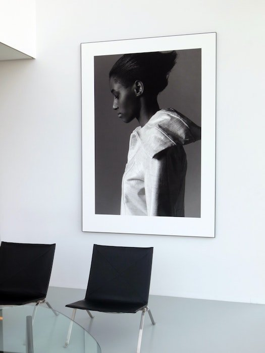 An enlarged black and white photo of a woman framed and hung on a living room wall