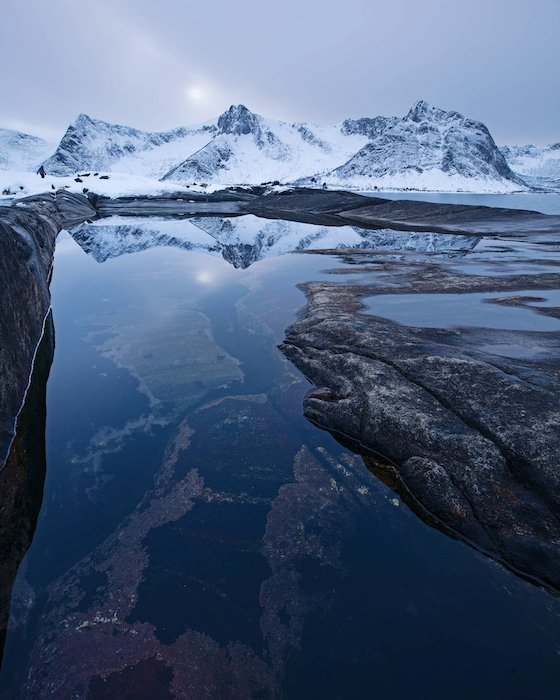 still water mirrors snowy mountains in the winter landscape