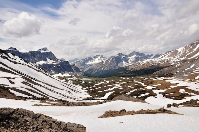 A landscape photo of mountains clouds blue sky and a rocky barren ground with snow