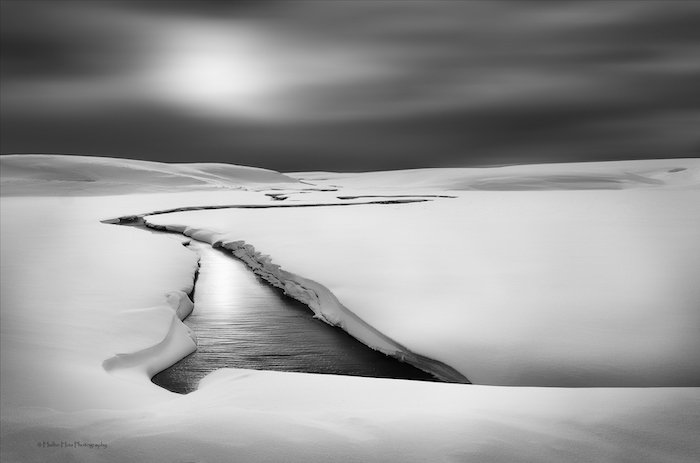 black and white landscape photography: a slow river flowing through untouched snow