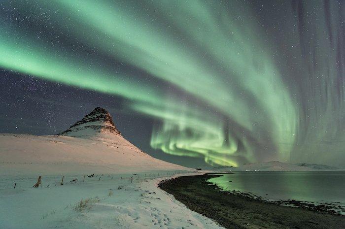 aurora borealis photographed shining above a snowy landscape