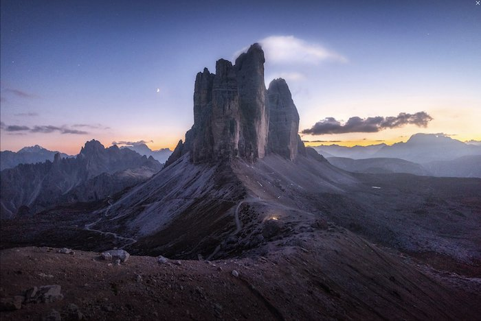 landscape photography inspiration: tall rock face in front of a sunrise