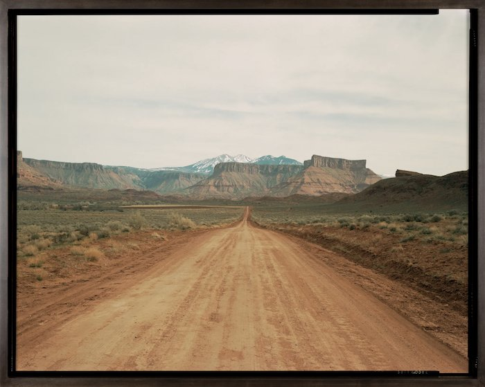 desert landscape: a lonely dirt road leading to a rocky ridge