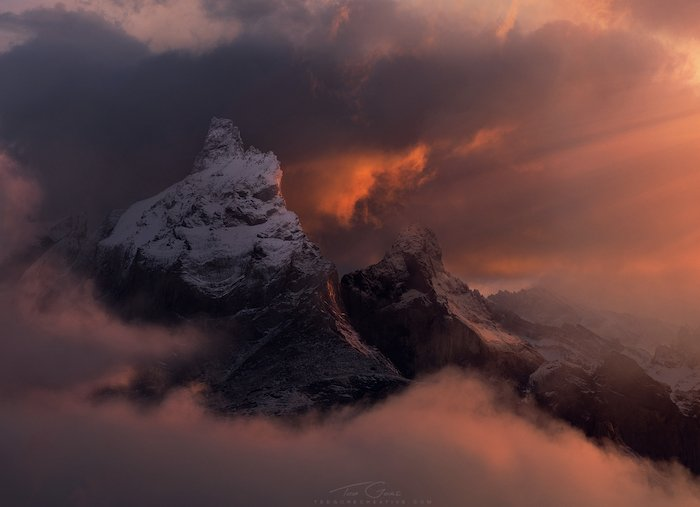 dramatic landscape photography: fog and clouds surround a snow-capped peak