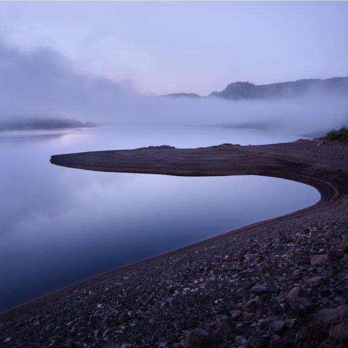 landscape photography: a layer of fog floats above a rocky shoreline