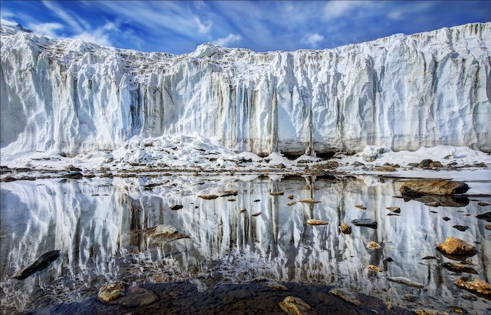 impressive landscape photography: face of a glacier mirrored on still water